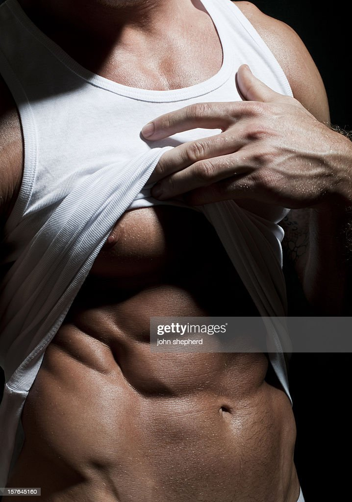Muscular male lifting t-shirt
