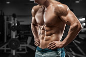 Muscular man abs in gym, shaped abdominal. Strong male naked torso, working out