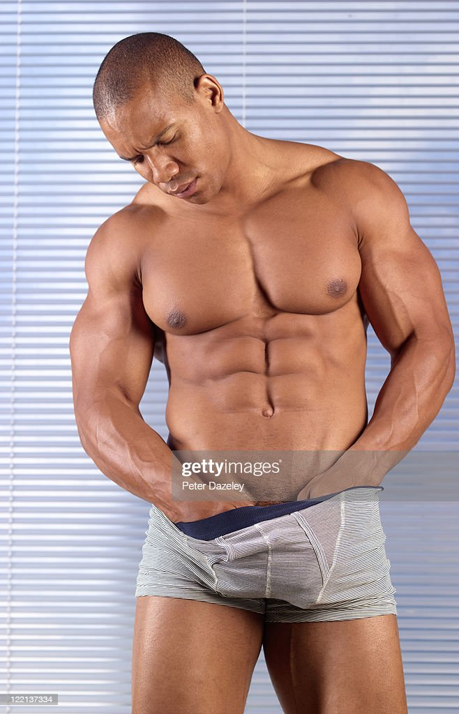 muscular man checking for testicular cancer : Stock Photo