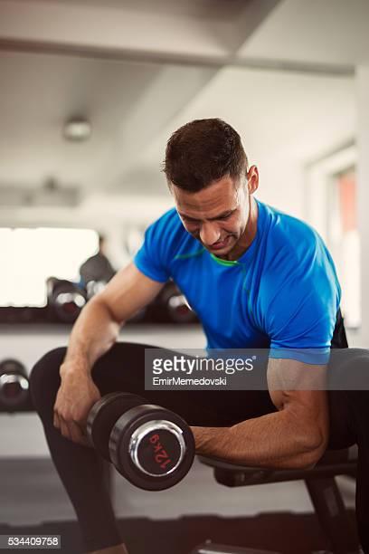 Hombre musculoso haciendo bíceps rizos con una pesa.