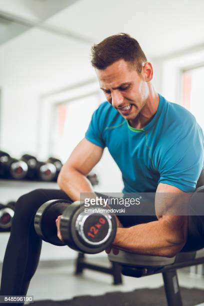 Muscular man doing bicep curls with a dumbbell.