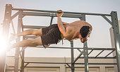 Muscular man doing exercises on horizontal bar hanging on one hand. Calisthenics workout.