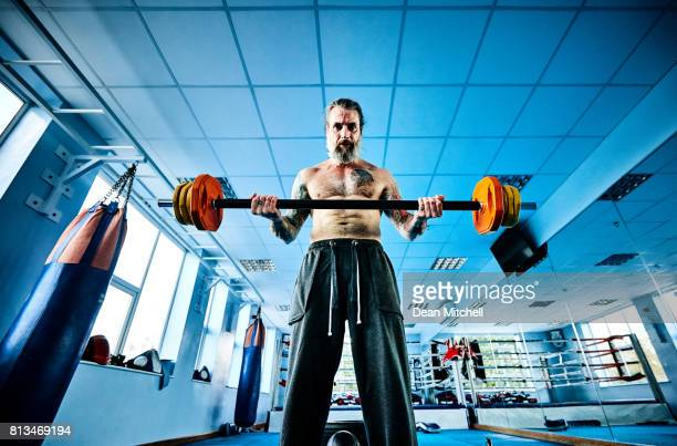 Muscular man exercising with barbell at the gym