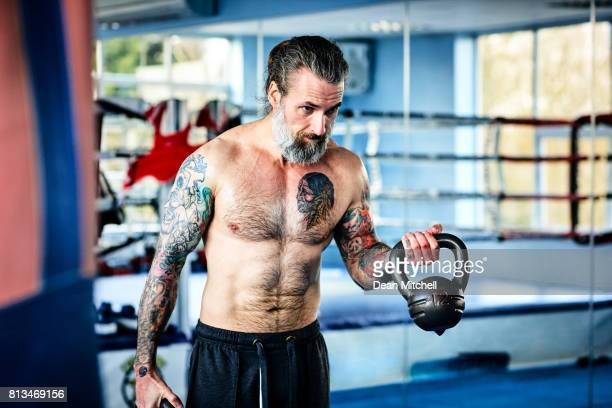 Muscular man exercising with kettle bell at the gym