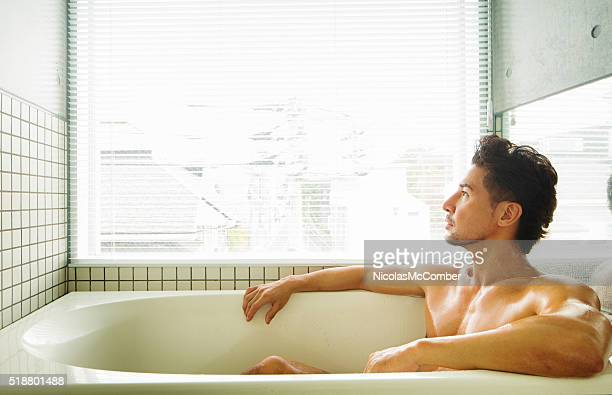 Muscular man looking pensively out of window while bathing