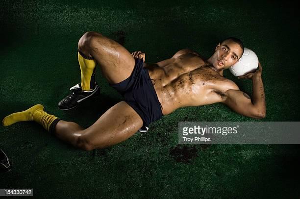 Muscular man lying on grass with soccer ball under head, studio shot