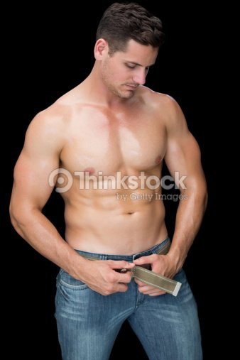 0683e61a Muscular Man Posing In Blue Jeans Stock Photo | Thinkstock