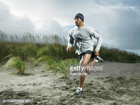 Muscular man running on beach : Stock-Foto