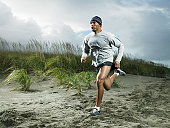 Muscular man running on beach