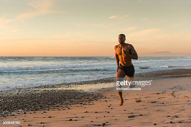 Muskel Mann läuft am Strand bei Sonnenuntergang