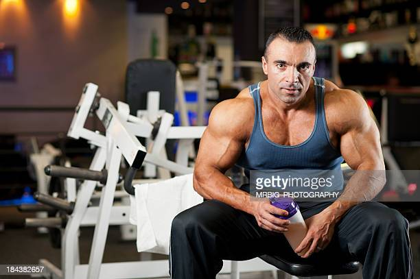 A muscular man sitting in the gym