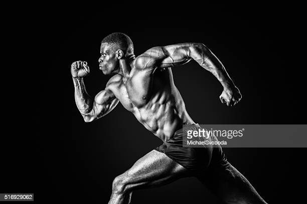 Muscular Man Sprinting On A Black Background