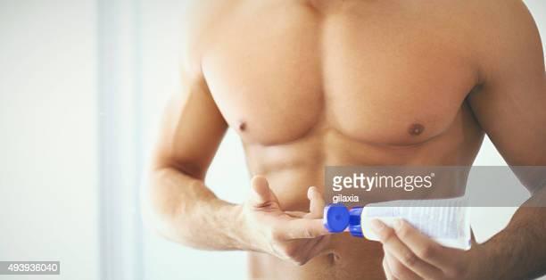 Muskuläre Mann mit Feuchtigkeitscreme.