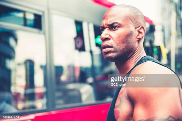 Homme musclé en attente devant un bus pour elle de passer