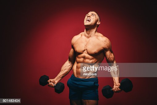 Muscular man with dumbbells screaming in pain : Stock Photo