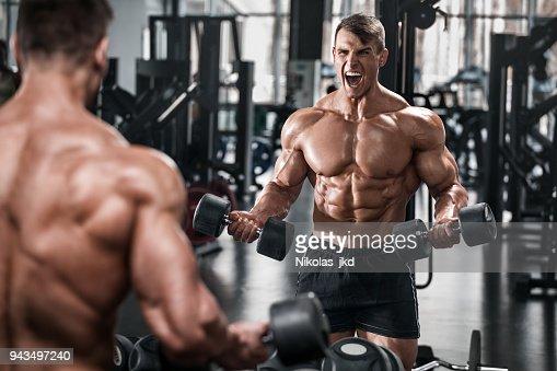 Hombre trabajando en el gimnasio haciendo ejercicios, abs fuerte torso desnudo masculino : Foto de stock