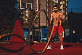 Muscular man workout with ropes outdoor on basketball court
