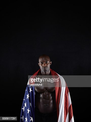 Muscular man wrapped in the American flag : Stock Photo