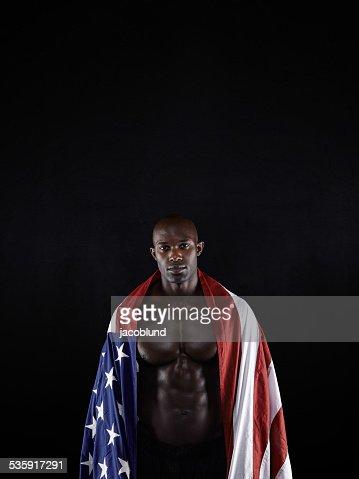 Muscular man envuelto en la bandera estadounidense : Foto de stock