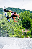 Muscular wakeboarder doing airborne stunt