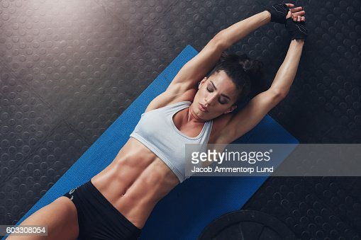 Muscular woman doing stretching workout on exercise mat : Stock Photo