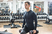 Muscular young man doing lunge exercise with weights in gym