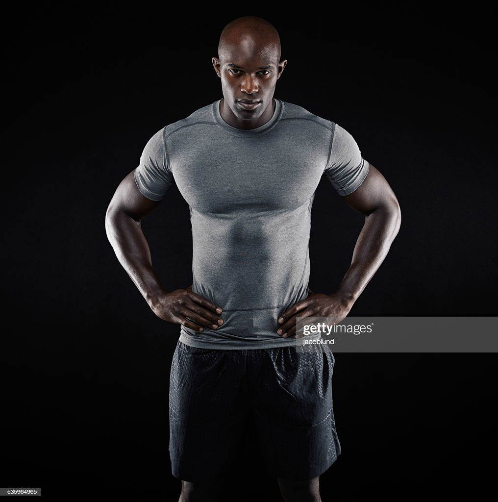 Muscular young man in sportswear on black background : Stock Photo