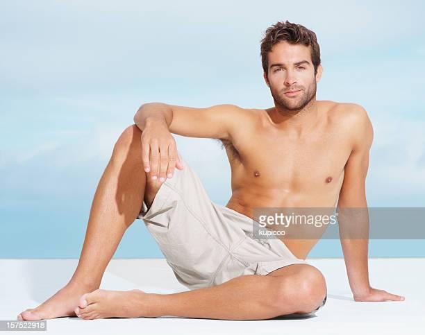 Muscular young man sittingoutside in the sun