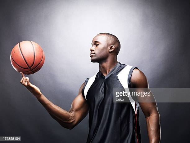 Muscular young man spinning basketball on finger
