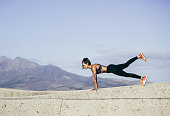 Muscular young woman doing push ups. Side view shot of healthy young female doing core workout outdoors.