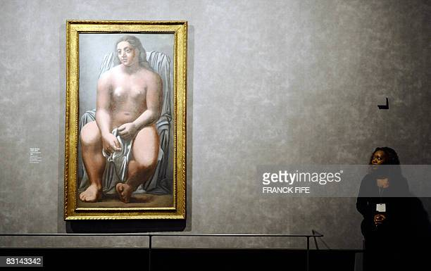 A museum attendant looks at a painting by Spanish painter Picasso 'Grande Baigneuse' during the exhibition 'Picasso and Masters' on October 6 2008 at...