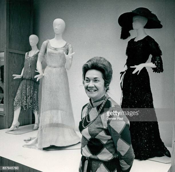 Museum curator Imelda De Graw poses with from left a dress with irregular hemline from the 20s a white beaded gown of 1910 and a black sequin...