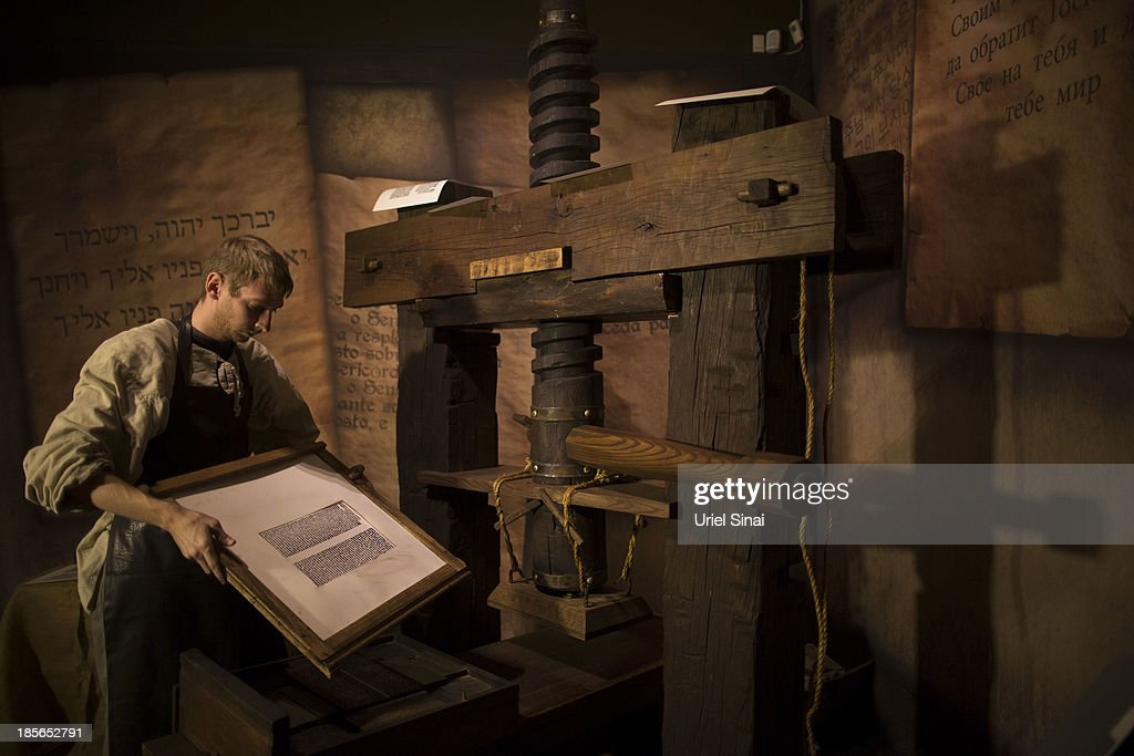 A museum employee shows how a Johannes Gutenberg replica printing press is used at the 'Book of Books' exhibition in the Bible Lands Museum on October 23, 2013 in Jerusalem, Israel. The exhibition contains more than 200 of the rarest biblical manuscripts, including original fragments from the Septuagint and the earliest New Testament Scriptures. This exhibition opened in Israel before heading to the Vatican and ends in Washington D.C, where it will be permanently displayed.