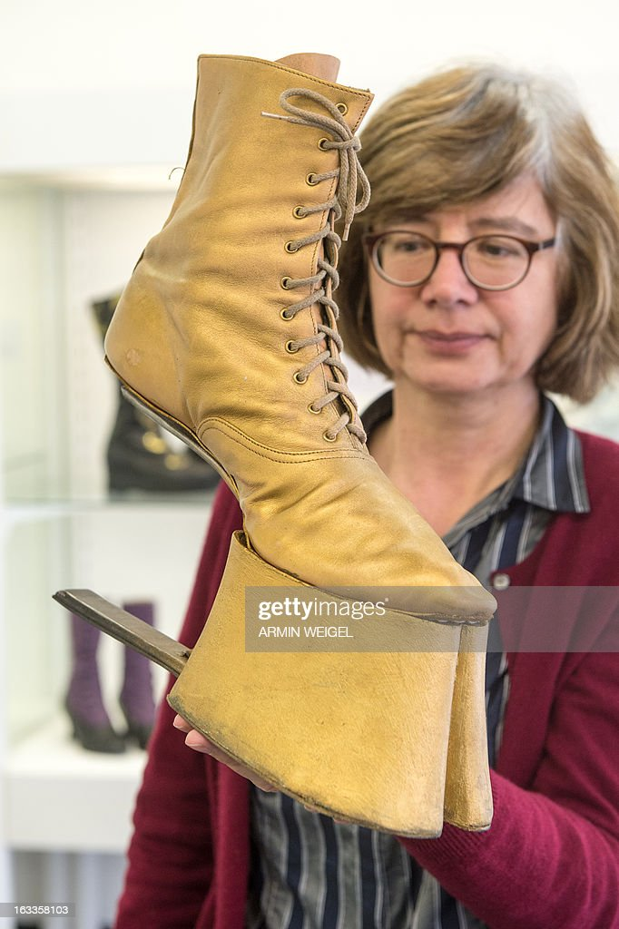 Museum employee Ulrike Schwarz holds a horse lace boot made by shoemaker Barbara Kistner for the rock opera 'Black Rider', on display at the Crafts Museum in Deggendorf, southern Germany, on March 7, 2013. The exhibition titled 'Zeigt Her Eure Schuh...' (Show Your Shoes) is running from March 10 to May 12, 2013 and displays creativity and variety of German shoemakers. AFP PHOTO / ARMIN WEIGEL GERMANY OUT