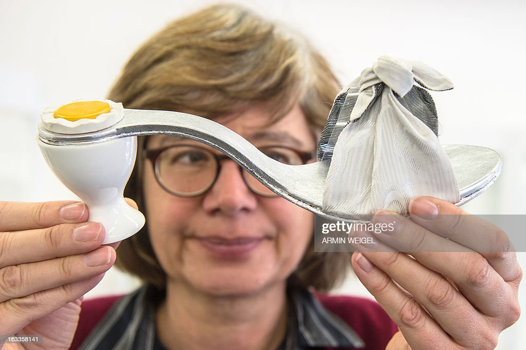 Museum employee Ulrike Schwarz holds up a shoe titled 'Breakfast' by shoemaker Verena Baehr at the Crafts Museum in Deggendorf, southern Germany, on March 7, 2013. The exhibition titled 'Zeigt Her Eure Schuh...' (Show Your Shoes) is running from March 10 to May 12, 2013 and displays creativity and variety of German shoemakers. AFP PHOTO / ARMIN WEIGEL GERMANY OUT