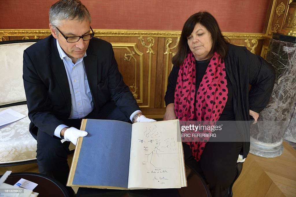 Museum of Letters and Manuscripts administrator Pascal Fulacher (L) and relative of French Artist Jean Cocteau Dominique Marny (R) pose presenting the script of the Jean Cocteau's movie 'La Belle et la Bete' (Beauty and the Beast), on September 19, 2013 in Paris.