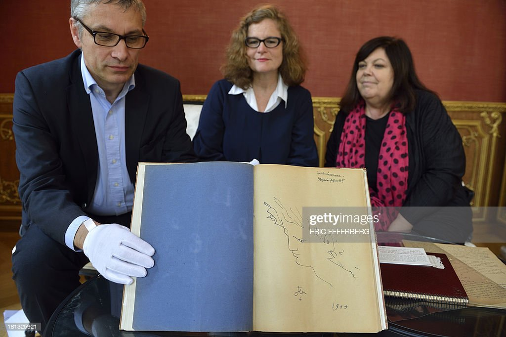 Museum of Letters and Manuscripts administrator Pascal Fulacher (L), M6 broadcast group member Ellen Schafer (C) and relative of French Artist Jean Cocteau Dominique Marny (R) pose presenting the script of the Jean Cocteau's movie 'La Belle et la Bete' (Beauty and the Beast), on September 19, 2013 in Paris.