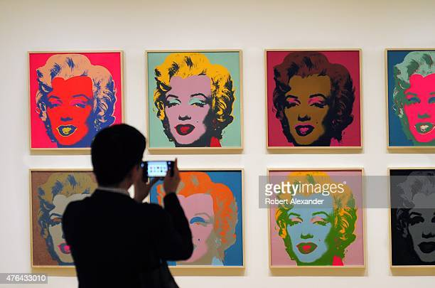 Museum of Modern Art visitor takes a picture of silkscreen portraits of Marilyn Monroe by Andy Warhol on display at the museum in Midtown Manhattan...