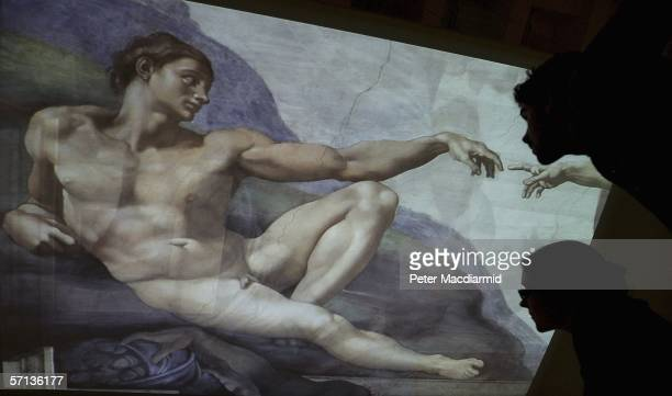 Museum staff look up at a projection of Michelangelo's 'Creation of Adam' at the 'Michelangelo Drawings Closer to the Master Exhibition' at The...