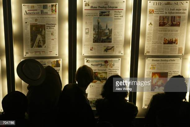 Museum visitors browse newspaper front pages from around the nation March 3 2002 at the Newseum in Arlington VA The Newseum closed its doors for the...