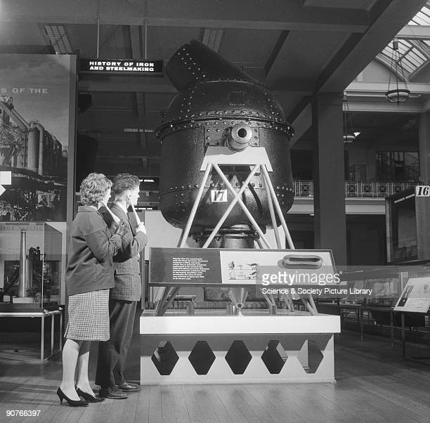 Museum visitors looking at a Bessemer converter using a handheld radio receiver and earphone intended for receiving signals from a lowpowered...