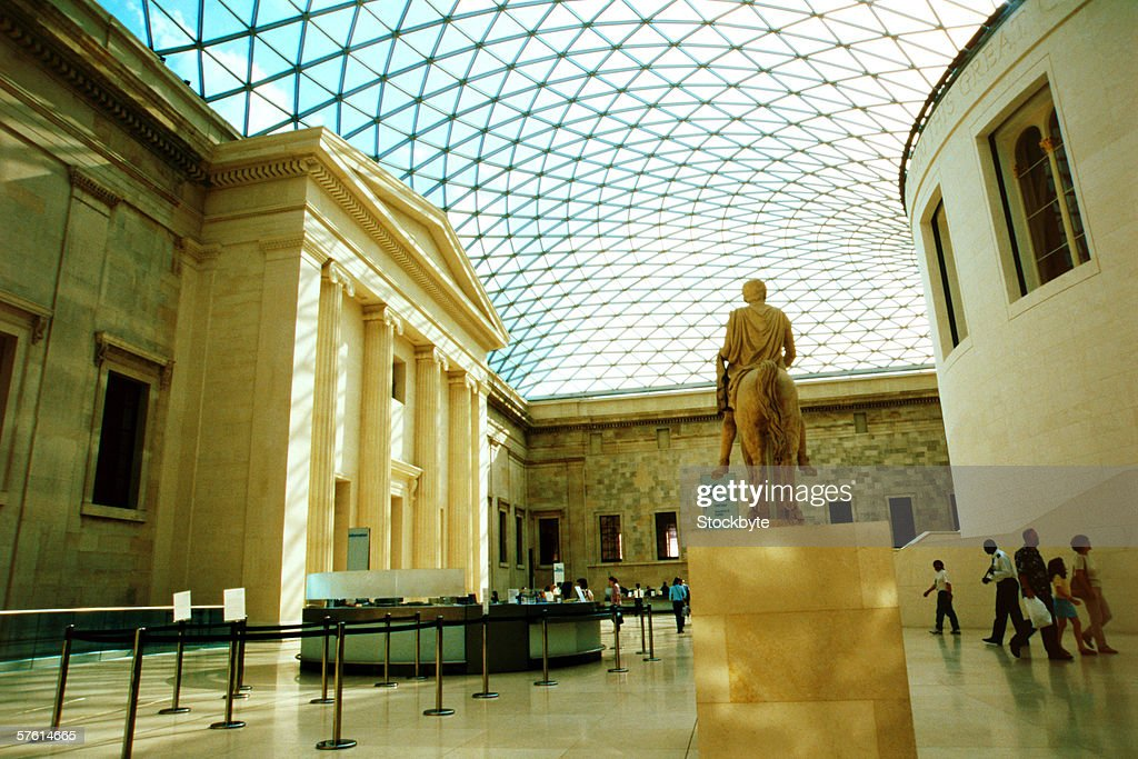 A museum with a monument in the center of the floor and people admiring it : Stock Photo