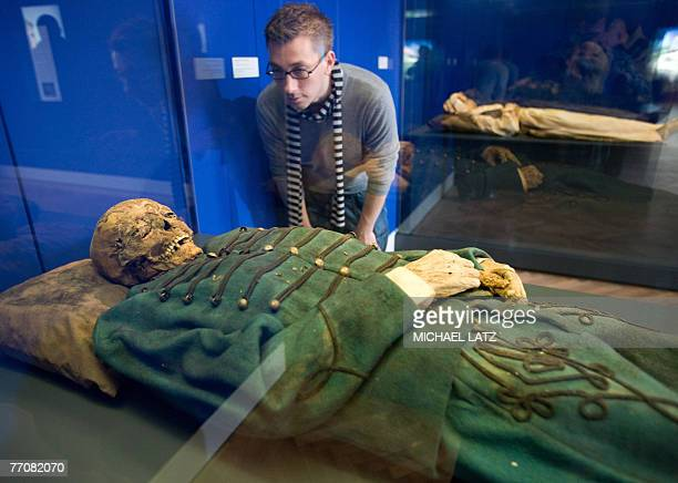 A museum worker looks at a 17th century mummy found in a Hungarian church at the 'Mummies The Dream of Everlasting Life' exhibition at the...