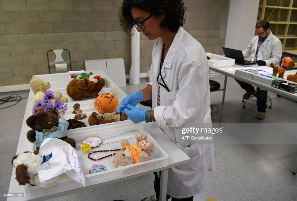 Museum workers catalogue objects collected at Las Ramblas makeshift memorial, set up following the August, 17 Barcelona jihadist attack, and stored to be catalogued and preserved at the Museu D'Historia de Barcelona (MUHBA) on September 13, 2017 in Barcelona. /