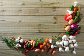 Vegetarian concept. Top view of fresh mushrooms, vegetables, greens and spices on wooden background