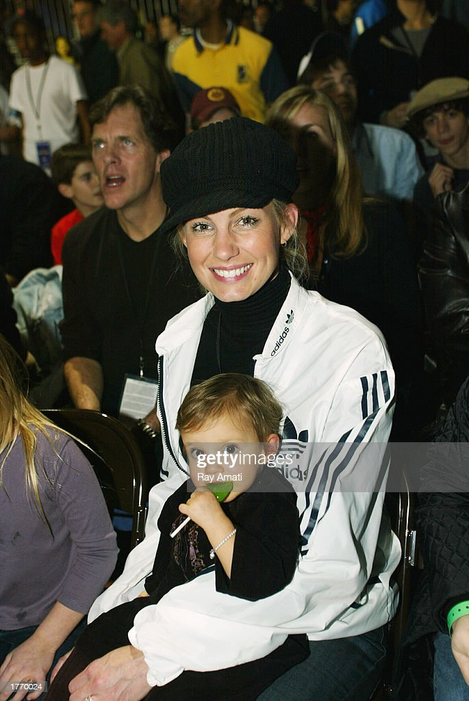 Music artist Faith Hill and her child pose for a photo while watching the Celebrity Game at the NBA Jam Session at the Georgia World Congress Center...