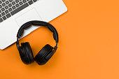 Headphones and laptop on orange background