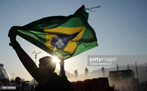 A music fan carries a Brazilian national flag on the second day of the Rock in Rio music festival at the City of Rock park in Rio de Janeiro Brazil...