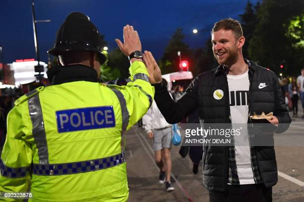 A music fan highfives a police officer as fans leave Old Trafford Cricket Ground following the One Love Manchester benefit concert for the families...