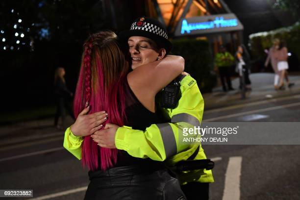 A music fan hugs a police officer as fans leave Old Trafford Cricket Ground following the One Love Manchester benefit concert for the families of the...